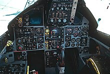Cockpit of jet fighter with circular dials and gauges. A control stick protrude from between where the pilot's legs would be.