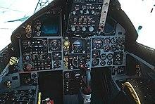 Cabina de avión de combate con indicadores y diales circulares: una palanca de control sobresale de entre donde estarían las piernas del piloto.