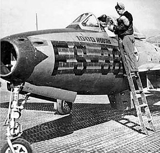 """182d Fighter Squadron - U.S. Air Force Captain John McMahn and Sergeant White of the 182nd Fighter-Bomber Squadron, Texas Air National Guard, close out flight records at Taegu Air Base, South Korea, following their Republic F-84E-15-RE Thunderjet (s/n 49-2360, nicknamed """"Miss Jacque II"""") becoming the first such aircraft to complete 1,000 flying hours, 1952. Note the mission markers."""