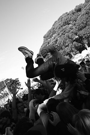 English: A member of the audience crowd surfin...