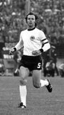 A black-and-white photograph of a dark-haired soccer player in white shirt, black shorts and white socks running towards the viewer.