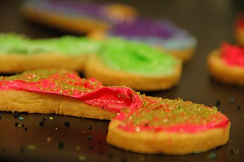 Frosting and sanding sugar on cookies.