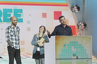 Three people, two women and a man, stand on an awards stage with a podium.