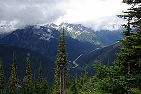 A forested valley under misty peaks, with the Trans-Canada Highway running through