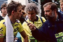 LeMond standing on the left of the picture in his racing jersey, being interviewed by a reporter