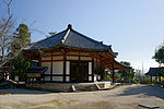 A small wooden octagonal building with white walls on a stone platform.