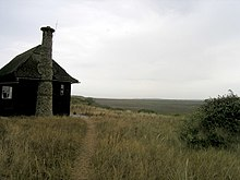 a large wooden hut with a stone chimney, standing in a grassy landscape