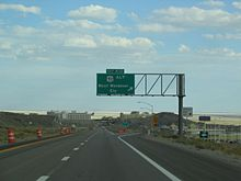 "gantry sign stating ""Exit 410—US-93 Alt—West Wendover—Ely"" as a freeway descends into a town with salt flats in the background."