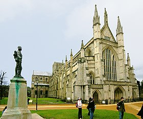 This exterior view at Winchester, taken from near the north west corner of the cathedral, and with a war memorial statue in the foreground, looks acutely along the north side of the building, showing it receding into the distance.