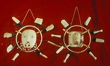 Photo of two masks: In the center is the image of a face, surrounded by a ring, in turn surrounded by eight white rectangular pieces.