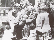 Riley seated in a chair surrounded by children