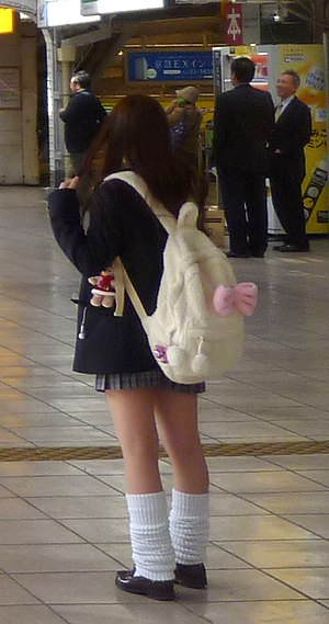 Kawaii - Kogal girl, identified by her shortened skirt. The soft bag and teddy bear that she carries are part of kawaii.