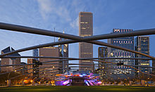 Evening view of a green lawn under a lattice with a lit metal bandshell against a backdrop of skyscrapers