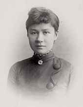 Black and white formal head shot photo of a young woman, with an easy expression and slight smile