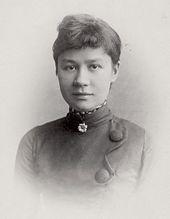 Foto de disparo a la cabeza formal en blanco y negro de una mujer joven, con una expresión fácil y una leve sonrisa