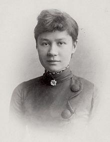 Uma fotografia, retrato em preto e branco à altura do peito, de uma jovem mulher com expressão leve