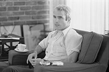 White-haired man in thirties sitting in a chair, pack of cigarettes readily available