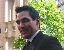 Chest view of a man with short black hair and wearing a suit. He smiles as he looks at the photographer.