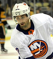 "A Caucasian ice hockey player wearing a white jersey with a blue and orange circular logo with the word ""OILERS"""