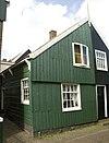 foto van Perceelsgedeelte van een houten huis met brede topgevel