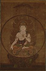Frontal view of a deity seated on a pedestal in lotus position embellished with ornaments. The right arm is hanging down supported by the legs with the palm of the right hand facing forward. The left hand is placed in front of the body.