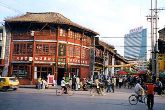 Kunming - An old wooden house and a modern skyscraper in the background