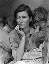 A haggard middle-aged woman in looks plaintively into the distance. Two children bury their faces into her shoulders. The woman and children are both dressed in shabby, drab clothing.