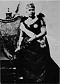 Liliuokalani standing next to chair draped with feather cloak.jpg