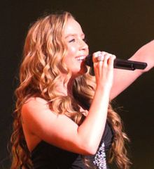 Photograph of Lisa Lavie singing with right hand holding microphone and left arm upraised