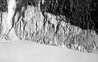 1958 Lituya Bay megatsunami - Part of the south shore of Lituya Bay showing the trimline, with bare rock below
