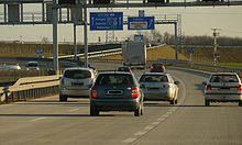 A view of the motorway from a carriageway, showing three traffic lanes and directional traffic signs mounted in a gantry