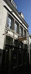 foto van Huis met lijstgevel, voorzien van gekoppelde segmentboogvensters in hardsteen, onderling verbonden door verticale reliefbanden.