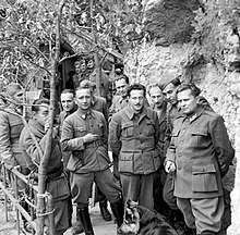 a black and white photograph showing half a dozen men standing on a narrow wooden walkway alongside a rock wall