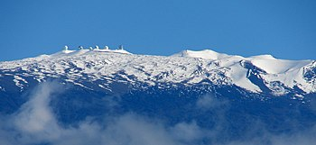 snow-covered peak with observatory domes