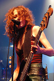 Melissa Auf der Maur singing into a microphone while playing a bass guitar.