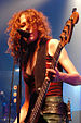 Melissa Auf der Maur—a Caucasian woman with long red hair wearing a red top and leather skirt—plays bass guitar and sings into a microphone