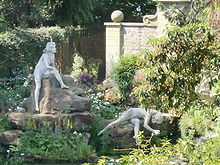 Colour photograph, zoom shot through trees of two nude female statues on a rockery, one sitting, the other in a strange pose
