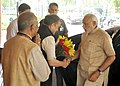 Narendra Modi being received by the Union Minister for Rural Development, Panchayati Raj, Drinking Water and Sanitation, Shri Chaudhary Birender Singh, on his arrival for the programme on National Panchayati Raj Day.jpg