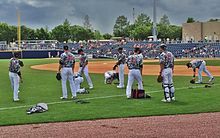 Baseball players wearing white pants, olive and tan camouflage jerseys, and black hats, on a green baseball field stretching before a game.
