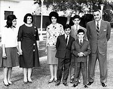 A group of related people posing outdoors. From left to right, there are three women dressed in shirts and long skirts, three boys dressed in suits and ties and a man in a suit and tie