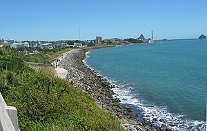 History of New Plymouth - View of the New Plymouth shoreline. The city is to the left and in the distance is Ngamotu and Sugar Loaf Islands, scene of the first European settlement.