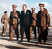 Three men walking side-by-side. The man in the middle is wearning a suit, while the two to his side are wearing military uniforms and hats. There are a few other men in uniform walking behind them