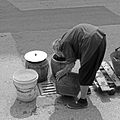 Old woman washing dishes in the street.jpg