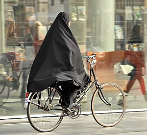 Islam in the Netherlands - Woman cycling on a sidewalk in a khimar in The Hague, on a Dutch bike.
