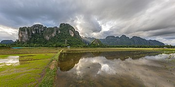 Panoramic of water reflection of the mountains of Vang Vieng with crepuscular rays and paddy fields.jpg