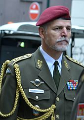 An older man with a gray beard, red beret, and olive green military suit.