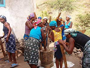 Husk - Women in Cape Verde using multiple pestles in a large mortar