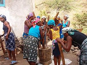 Husk - Women in Cape Verde using multiple pestles in a large mortar