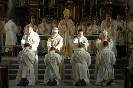 During the rite of ordination, after the bishop the priests present lay their hands on the ordinands Priesterweihe in Schwyz 2.jpg