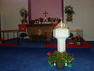 Pentecost - A Protestant church altar and font, decorated for Pentecost with red flowering plants and green birch branches